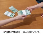 Woman hand giving pile of Polish money to woman hand. Wooden table background with piles of money. Polish money banknotes - stock photo