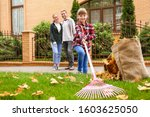 Family Cleaning Up Autumn...