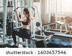 Small photo of Back view of healthy young caucasian woman doing lat pull pull down exercise in fitness gym