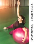 Small photo of Woman at the gym doing exercises with pilates ball with her hand rise up