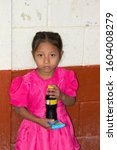 Small photo of Guatemala , Chiquimula – 2/5/15. Humble girl in rural area of Chiquimula north of Guatemala City, refreshing cola and cookie soda, colorful dress with innocent look. Editorial
