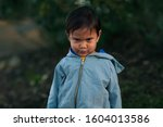 Small photo of A little boy in an outdoor setting with a negative facial expression that looks uncooperative and upset.