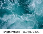 Small photo of Blue ocean water and waves being churned by a boat's motor.