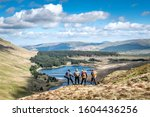 Small photo of SNOWDONIA, WALES- MAY, 2019: A gaggle of vagabond hikers overlooking a beautiful vista in Snowdonia National Park unknowing of what the forest below has in store for them that evening.