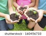 hands holding sapling in soil... | Shutterstock . vector #160456733