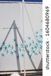 Small photo of Odessa / Ukraine - 06 22 2019: Blue bird pattern on white tent with crossed triangle shadow lines. Beach sunshade background with copy space. Summer vacation backdrop