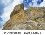 Small photo of View of a breakaway and overhanging rock against the sky. A cliff on Mount Alchak in Sudak in eastern Crimea.