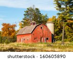 An Old Red Barn With Silo Is...