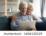 Small photo of 60s-70s couple plan vacation use pc, browse booking website, learn hotel or ticket options online, wife hugs from behind husband family enjoy virtual entertainment new apps, reading last positive news