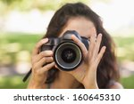 Front view of young brunette woman taking a picture in a park - stock photo