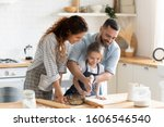 Small photo of Small adorable kid girl preparing pie with loving caring parents on domestic kitchen, young family enjoy cooking process at home, teaching child, spend weekend together, help, happy parenthood concept