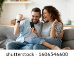 Small photo of Excited overjoyed couple resting on couch holding smart phone celebrating on-line lottery win, bid betting victory moment, unbelievable opportunity or invitation, internet sale, getting prize concept