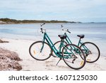 Two Bicycles Parked On A Beach...
