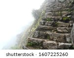 A view of Inca stairs at 2,400 m high in the Machu Picchu Mountain. Other side is cliff under heavy fog. Inca Trail, Peru.