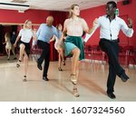 Small photo of Young smiling people practicing vigorous jive movements in dance class