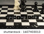 Small photo of The concept of Tantalize represented by black letter tiles with chessboard background