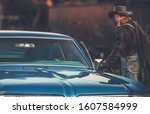 American Classic Ride. Caucasian Cowboy and His Vintage Classic Car. - stock photo