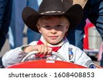 Goodwood, Sussex / UK - 14 Sept 2019: Portrait of smiling young boy, Briggs Griffin, behind the wheel of an Austin J40 pedal car. He wears a cowboy hat, red scarf and white overalls. Settrington Cup, - stock photo