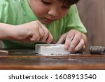 Small photo of Children having fun with archaeology excavation kit. Boy plays an archaeologist excavated, training for dig fossil