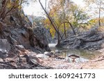 View on Potomac river with mountain cliff rocks in Great Falls park in autumn of Maryland with trees colorful foliage on Billy goat trail hike