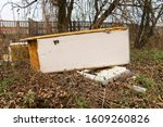 Small photo of Garbage, rubbish waste dumped in the environment. Wild landfill. Illegal dumping. The unauthorized, open dump of garbage. An old, broken fridge among bushes, shrubs by a concrete fence in the city.