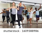 Small photo of Young smiling people practicing in pairs vigorous jive movements in dance class