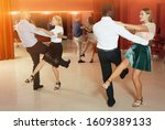 Small photo of Pairs of young positive people dancing vigorous jive movements in dance studio