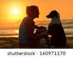 Stock photo woman with her cute dog in the beach on golden sunset background girl enjoying her pet friendship 160971170