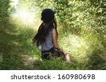 Girl In Black Hat Sitting On...