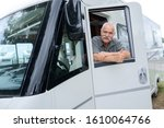 portrait of senior man with motorhome holding thumbs up - stock photo