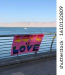 Small photo of Love is Love LGTBQ Sign over the Sea of Galilee