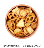 Salty cracker and pretzel snacks, party mix in clay bowl isolated on white background, top view
