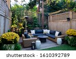 Small photo of Urban, neutral, outdoor living space exterior photo. Outdoor living room with couch, comfy couch cushions, throw pillows, love seat, chairs and coffee table. Backyard lush with greenery and plants.