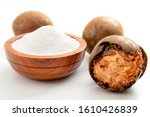 Small photo of Low calorie alternative to sugar and natural remedy for inflammatory disease and arthritis conceptual idea with Luo Han Guo or Monk fruit and bowl of powder sweetener isolated on white background