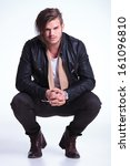 smiling young man in leather jacket standing crouched on light gray studio backgroun