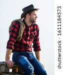Small photo of Thoughtful farmer thinking about business. Ranch worker. Eco farm. Farming concept. Handsome man in hat and rustic style outfit. Keep ranch. Life at ranch. Cowboy with lasso rope sky background.