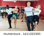 Small photo of Portrait of young positive people practicing vigorous jive movements in dance class