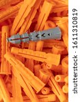 Small photo of Plastic dowel. Gray dowel on a pile of orange dowels. Construction dowel. Fasteners. Industrial background. Building background.