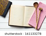 top view of old recipe book with kitchenware and napkin on white wooden table - stock photo