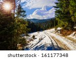 winter mountain landscape. winding road that leads into the pine forest covered with snow. wooden fence stands near the road. - stock photo