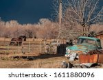 Antique warm front lit rusty light blue pickup truck sits near a rusty junk pile near an aged wooden structure under the stormy dark sky - stock photo