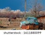 Antique rusty light blue pickup truck sits near a rusty junk pile near an aged wooden structure under the stormy dark sky - stock photo