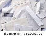 Small photo of Piles of used and torn business letter envelopes. Stacked of empty office mails, received, opened and read. Concept for business correspondence, bills to pay, fan mail or reader, viewer write ins.