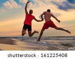 happy woman and man jumping on... | Shutterstock . vector #161225408