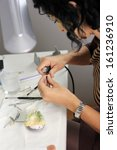 Small photo of dental technician processes the artificial teeth with micromotor
