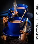 Delicious hot chocolate in a blue cups with chocolate candy and spices on a dark background. - stock photo