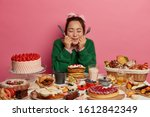 Small photo of Photo of lovely millennial girl holds knife and fork, thinks what to eat first, sits at big table full of cookies, pastries and cakes, eats different desserts during holidays, has bad eating habits