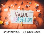 Small photo of Text sign showing Value Proposition. Conceptual photo feature intended to make a company or product attractive Colored crumpled papers empty reminder wooden floor background clothespin.