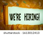 Small photo of Handwriting text We Re Hiring. Concept meaning recently employ someone or pay him to do particular job Paper clip and torn cardboard placed above a plain pastel table backdrop.