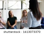 Small photo of Rear back view female african ethnicity participant at group rehab session telling story share personal problem with associates or corporate staff gathered together listening business coach at seminar
